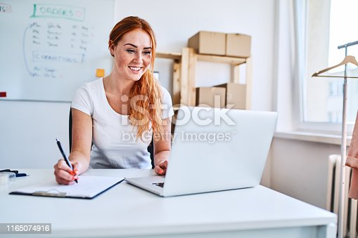 Female online business owner using laptop and documents in small office