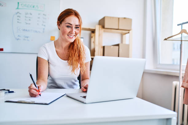 Female online business owner using laptop and documents in small office stock photo