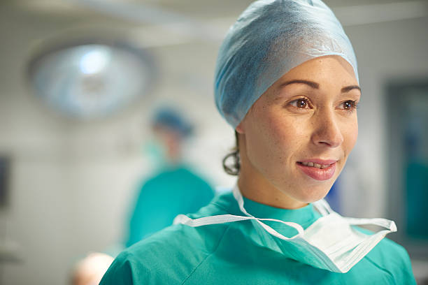 female operating room nurse or surgeon portrait a proud female operating nurse stands away from the operating table and looks off camera all proud. In the background the anaesthetist and surgeon are finishing off the operation or prepping it . anesthesiologist stock pictures, royalty-free photos & images