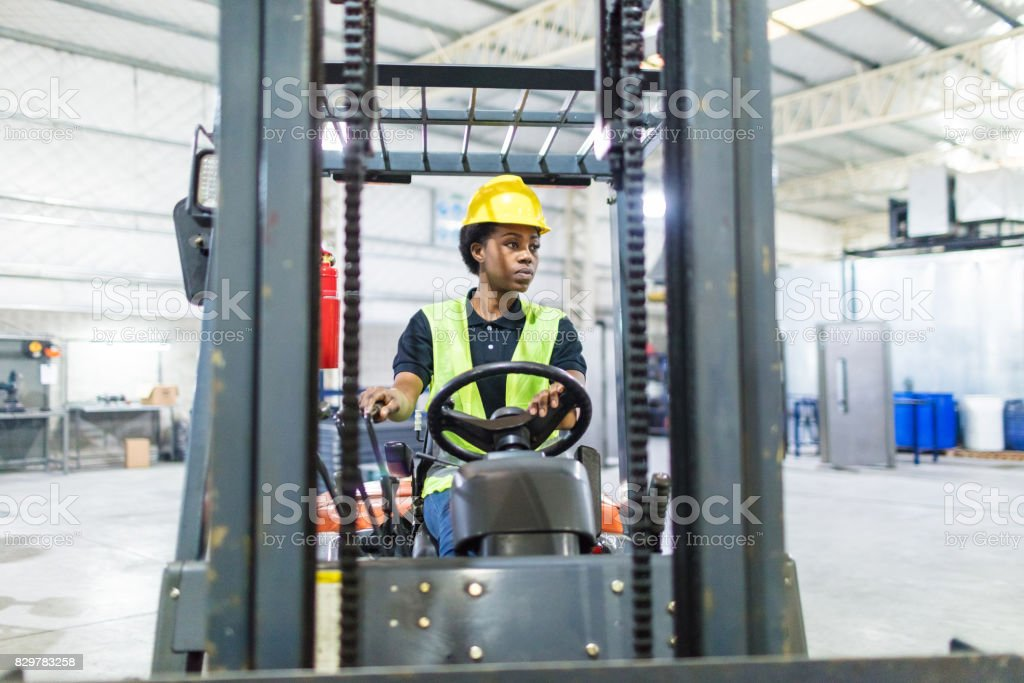 Female operator driving forklift in factory stock photo
