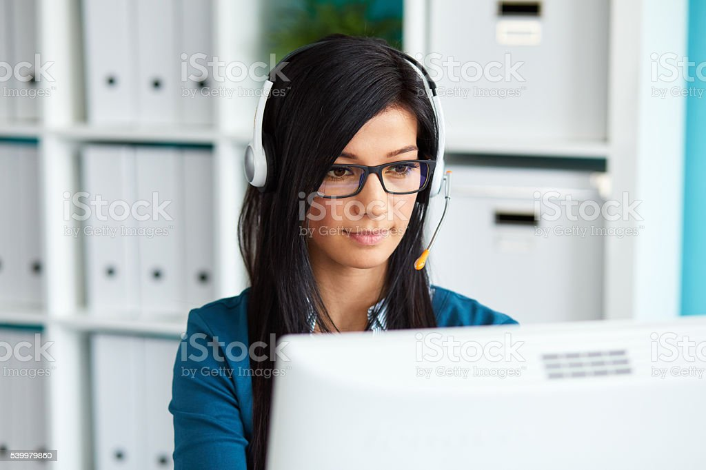 Female operator with headset Portrait of young female operator with headset using desktop computer in office Adult Stock Photo