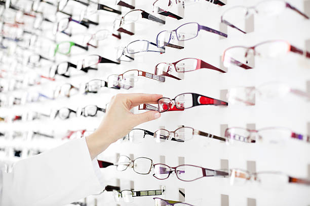 female optician suggest glasses - optical instrument stock pictures, royalty-free photos & images