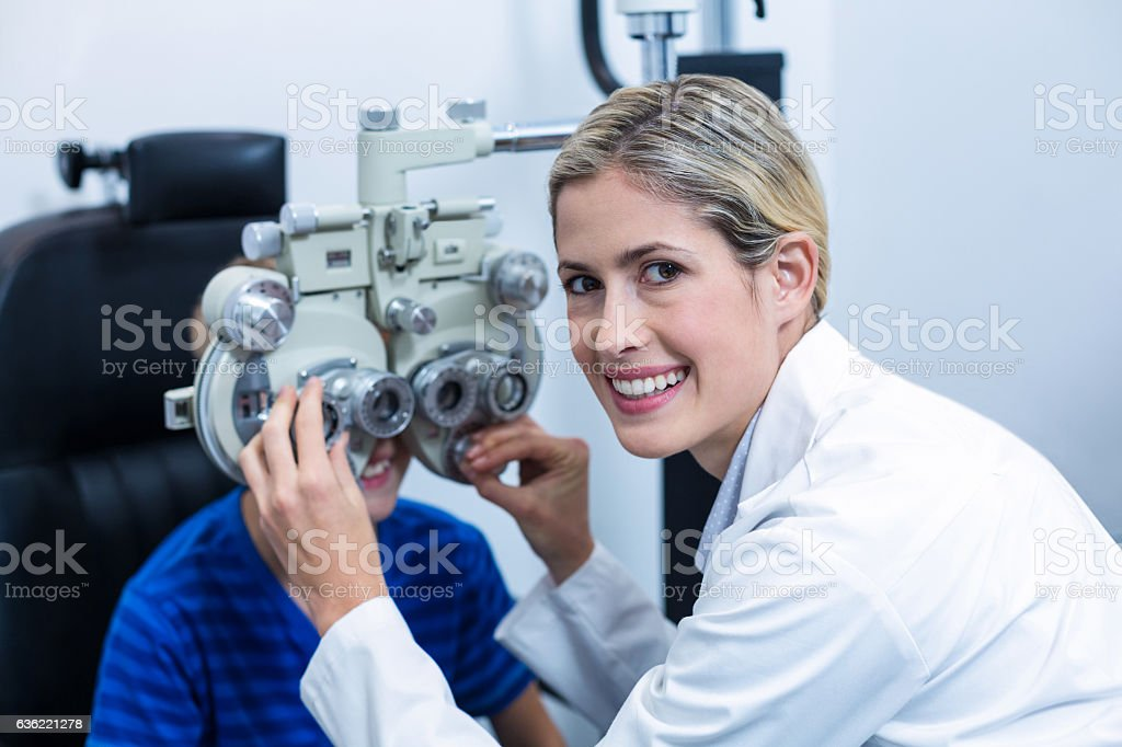 Female optometrist examining young patient on phoropter stock photo