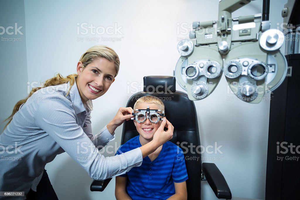 Female optometrist examining young patient with phoropter stock photo