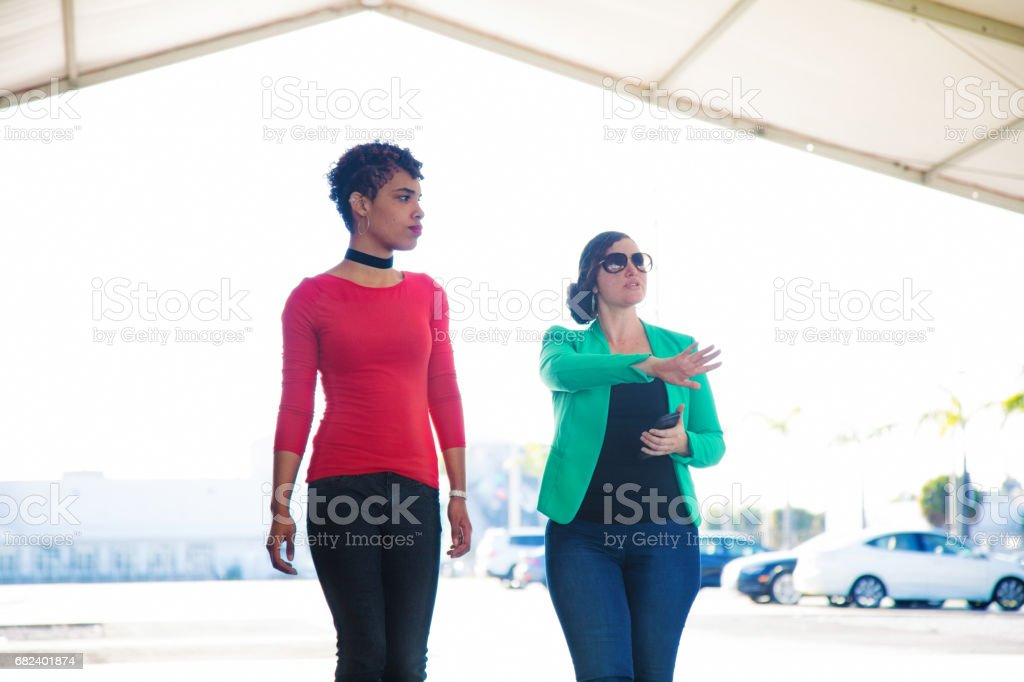 Female organizer discusses project outdoors with millennial female client royalty-free stock photo