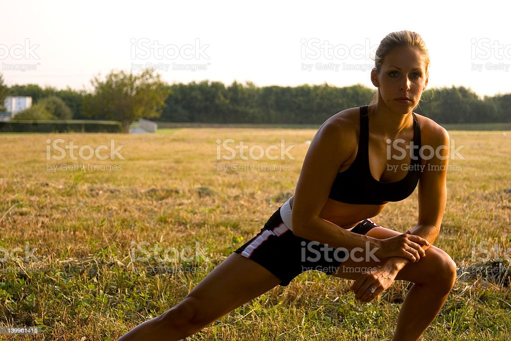 Female out in a field doing side lunge to the right stock photo