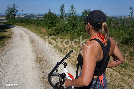Middle aged Women Wearing Sports Wear out on a Mountain bike stopped admiring a view across the fields with Blue sky standing on a gravel track that's leading away downhill.