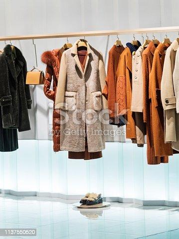 Female overcoat in modern clothing store.