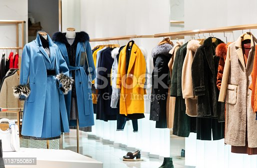 Female overcoat in modern clothing store.