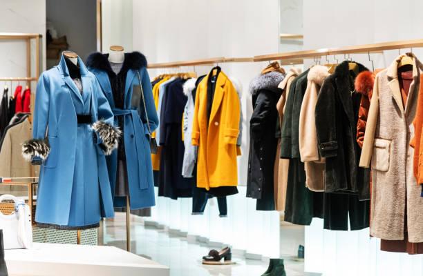 vrouwelijke jas in de moderne kleding winkel - kledingwinkel stockfoto's en -beelden