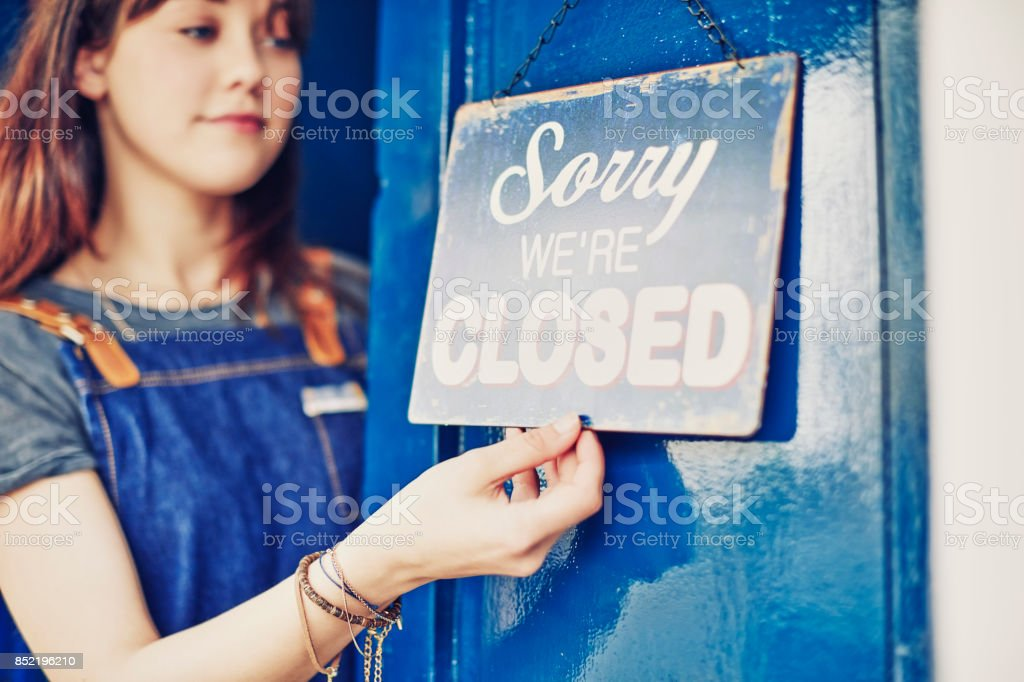 Female owner of delicatessen hanging closed sign on door stock photo