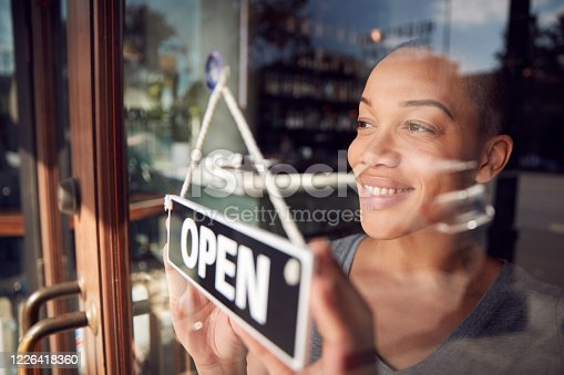 istock Female Owner Of Start Up Coffee Shop Or Restaurant Turning Round Open Sign On Door 1226418360