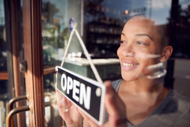 weibliche besitzerin von start up coffee shop oder restaurant drehen runde offene stürtisch - offen allgemeine beschaffenheit stock-fotos und bilder