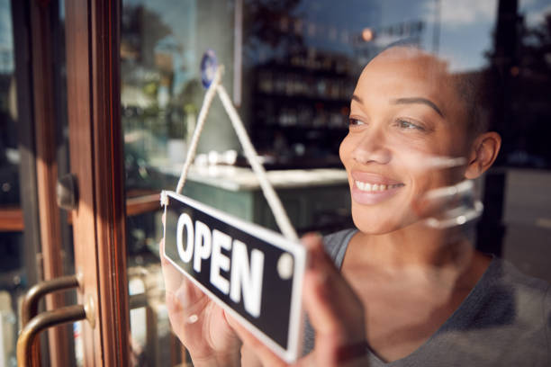 Female Owner Of Start Up Coffee Shop Or Restaurant Turning Round Open Sign On Door Female Owner Of Start Up Coffee Shop Or Restaurant Turning Round Open Sign On Door african american ethnicity stock pictures, royalty-free photos & images
