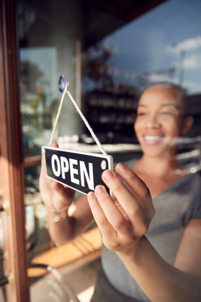 Female Owner Of Start Up Coffee Shop Or Restaurant Turning Round Open Sign On Door stock photo