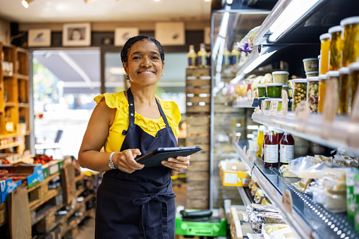 Portrait of smiling female owner checking inventory. Confident mature female owner is using digital tablet in deli. She is working in grocery store.