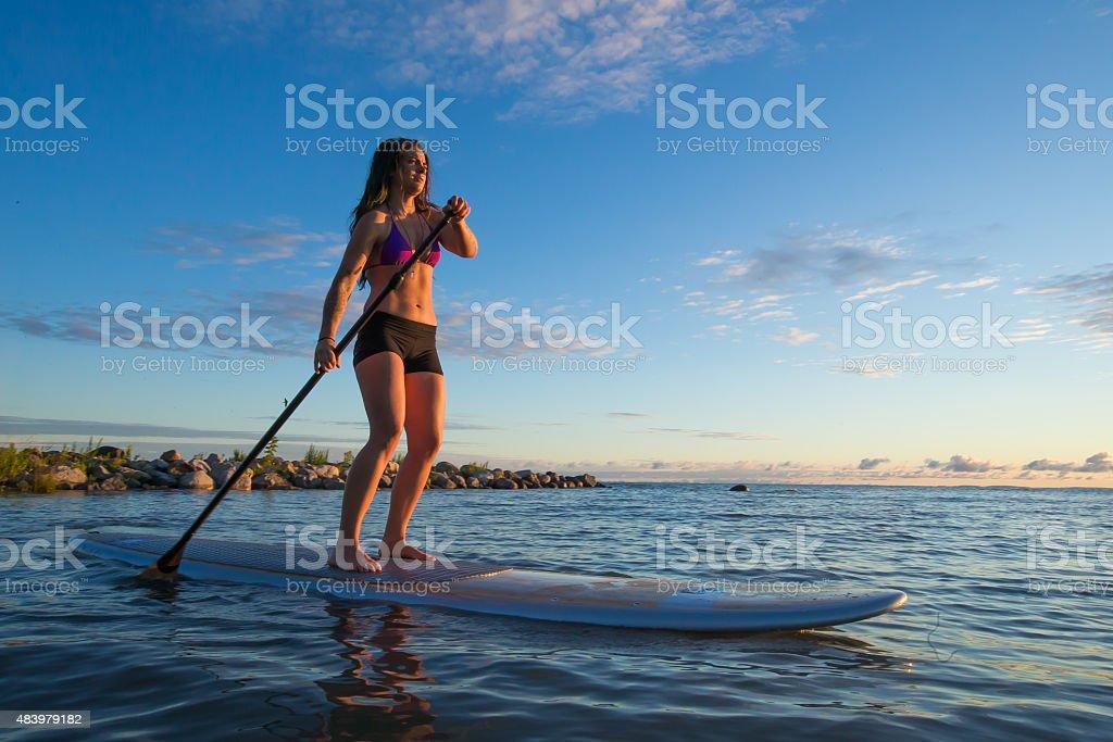Female paddleboarding at sunrise stock photo