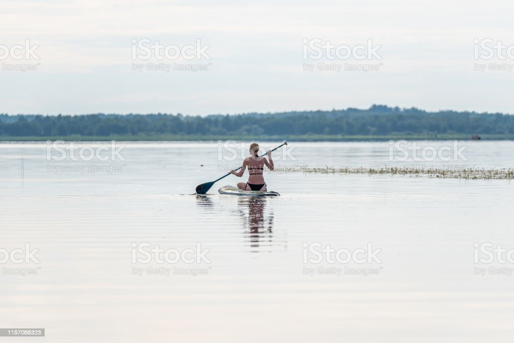 Female Paddler Sitting on a Stand Up Paddle Board on a Still Lake