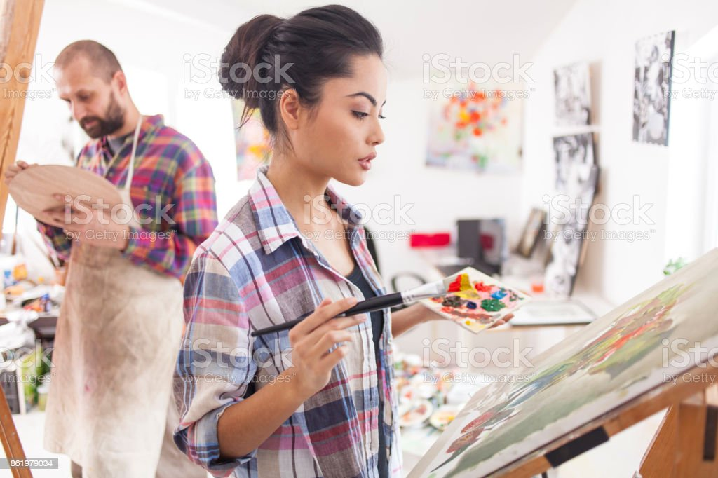 Female painter drawing in studio stock photo