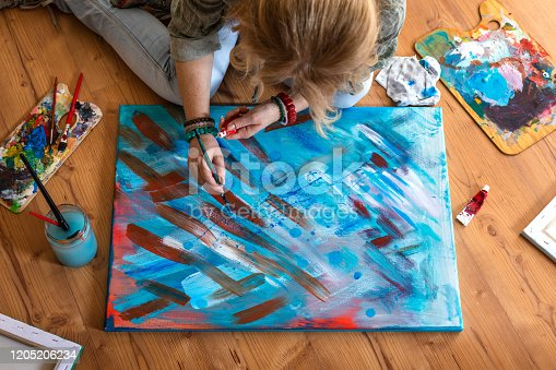910798810 istock photo Female painter finishing her abstract painting 1205206234