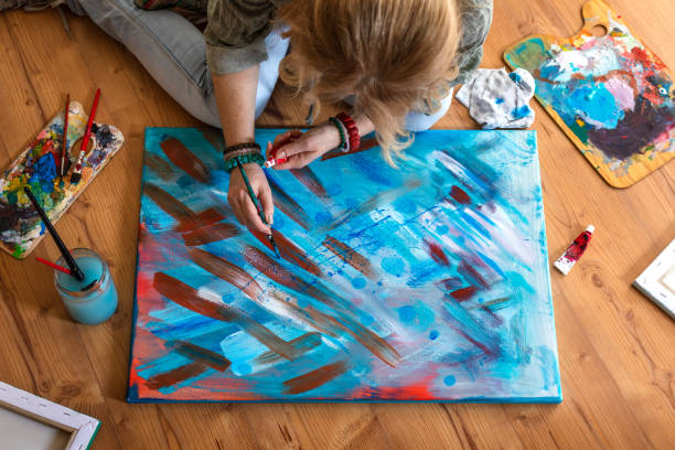 Female painter finishing her abstract painting stock photo