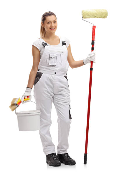 Female painter holding a paint roller and a color bucket Full length portrait of a female painter holding a paint roller and a color bucket isolated on white background bib overalls stock pictures, royalty-free photos & images