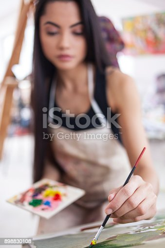 Portrait of female painter drawing in atelier. Wears casual clothes and apron, with long balck hair.