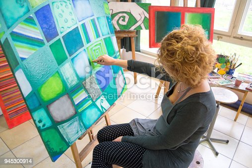 Female artist painting abstract paintings in her professional studio.