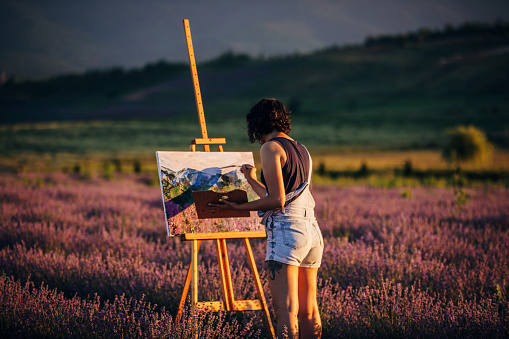 One woman, beautiful female painter artist painting on lavender field outdoors on a sunny day.