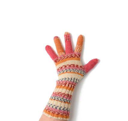 female palm in knitted multi-colored mittens on a white background, close up