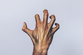 Creepy zombie hand close-up. Female palm with crooked fingers covered with golden glitter.