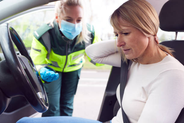 Female Paramedic Helping Female Driver With Whiplash Neck Injury Involved In Road Traffic Accident stock photo