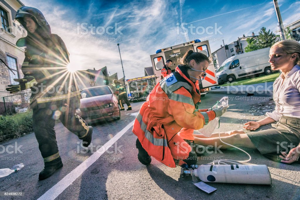 Female paramedic helping injured woman stock photo