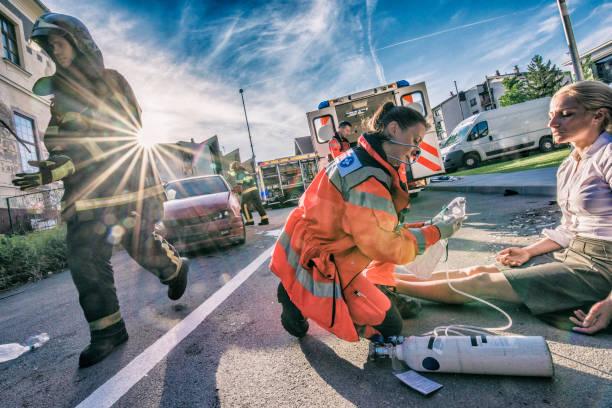 Female paramedic helping injured woman stock photo