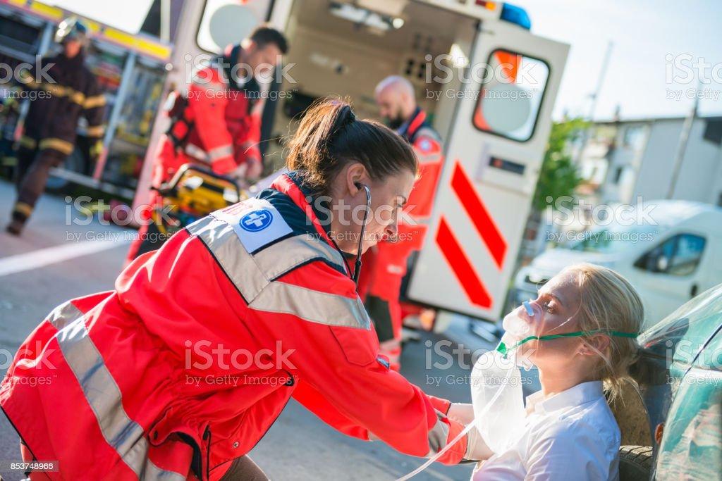 女性救急救命士を助ける女性が負傷しました。 ストックフォト