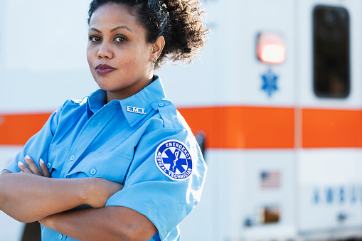 A female paramedic standing with arms crossed in front of an ambulance, looking at the camera. She is a mid adult woman in her 30s, mixed race Hispanic and Pacific Islander.