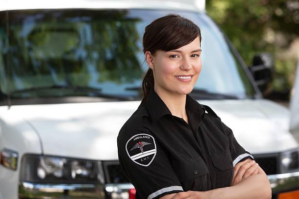 Female paramedic standing outside of her ambulance stock photo