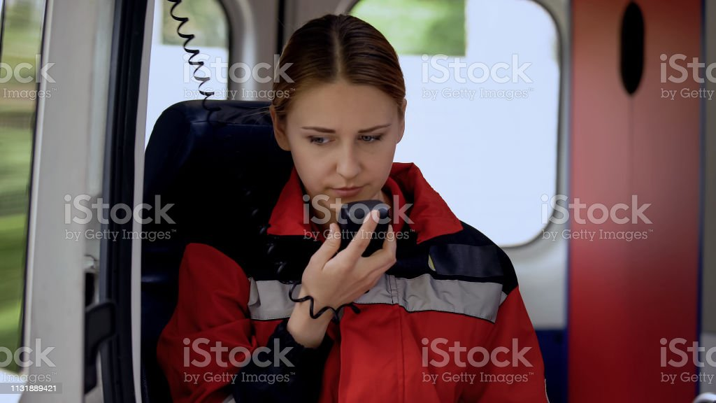 Female paramedic talking by radio in ambulance, ready to drive out on call stock photo