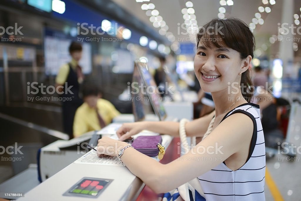 Female Passenger At Airport Ticket Counter stock photo