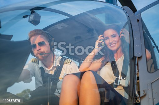 Smiling female passenger sitting in helicopter cockpit by the pilot and adjusting headphones