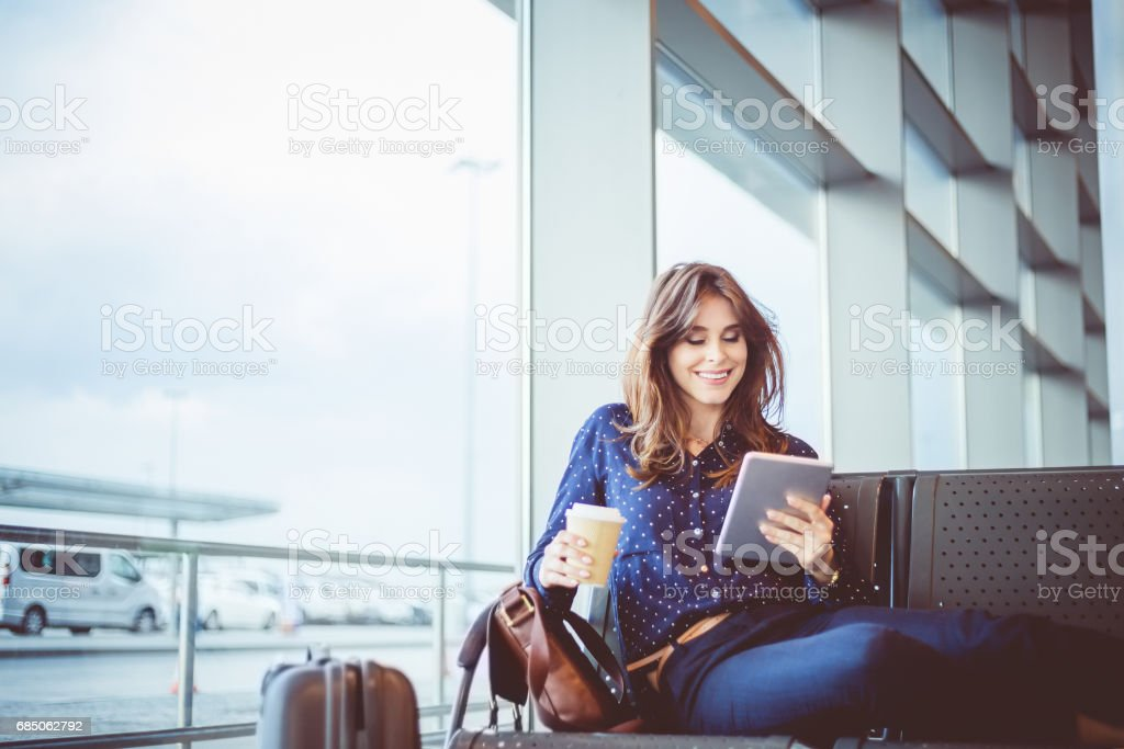 Female passenger waiting her flight at airport lounge stock photo
