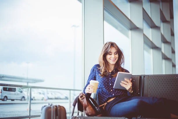 female passenger waiting her flight at airport lounge - business travel stock photos and pictures