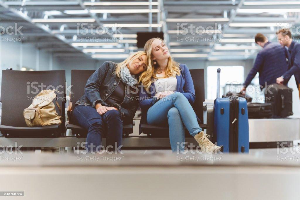Weibliche Passagiere schlafen in der Flughafen-lounge Lizenzfreies stock-foto