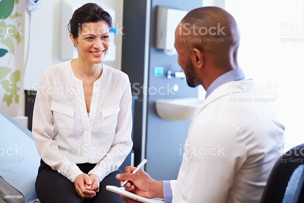 Female Patient And Doctor Have Consultation In Hospital Room stock photo