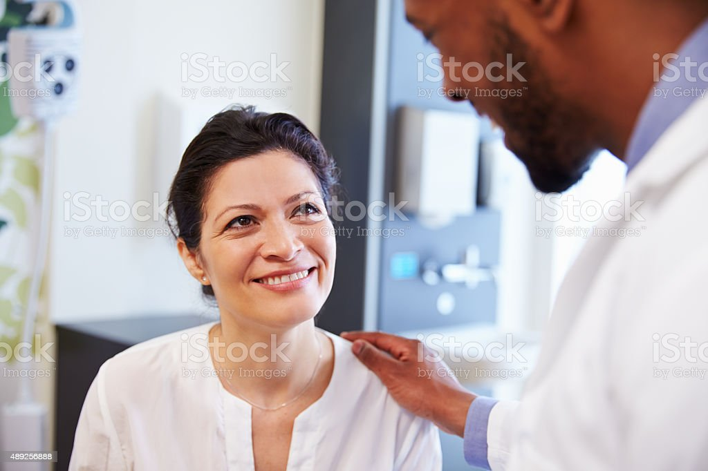 Female Patient Being Reassured By Doctor In Hospital Room stock photo