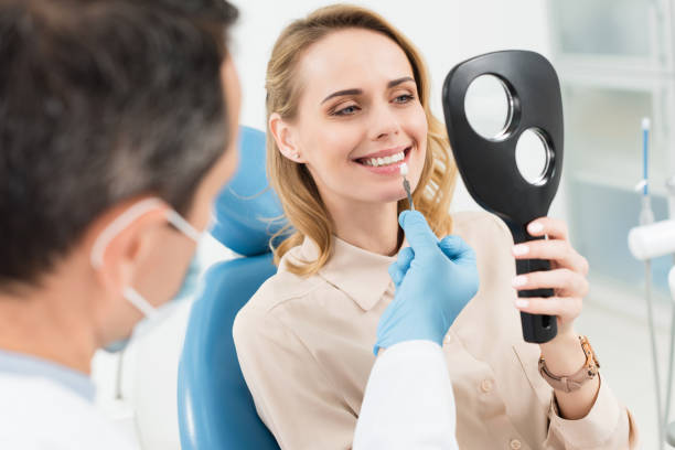 female patient choosing tooth implant looking at mirror in modern dental clinic - dental implants stock photos and pictures