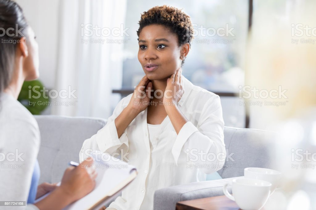 Female patient describes symptoms to doctor stock photo