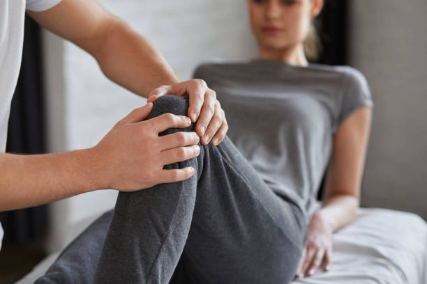 Female patient doing physical exercises with physiotherapist. Male therapist treating injured knee of young athlete.Post traumatic rehabilitation, sport physical therapy, recovery concept Female patient doing physical exercises with physiotherapist. Male therapist treating injured knee of young athlete.Post traumatic rehabilitation, sport physical therapy, recovery concept. sports medicine stock pictures, royalty-free photos & images