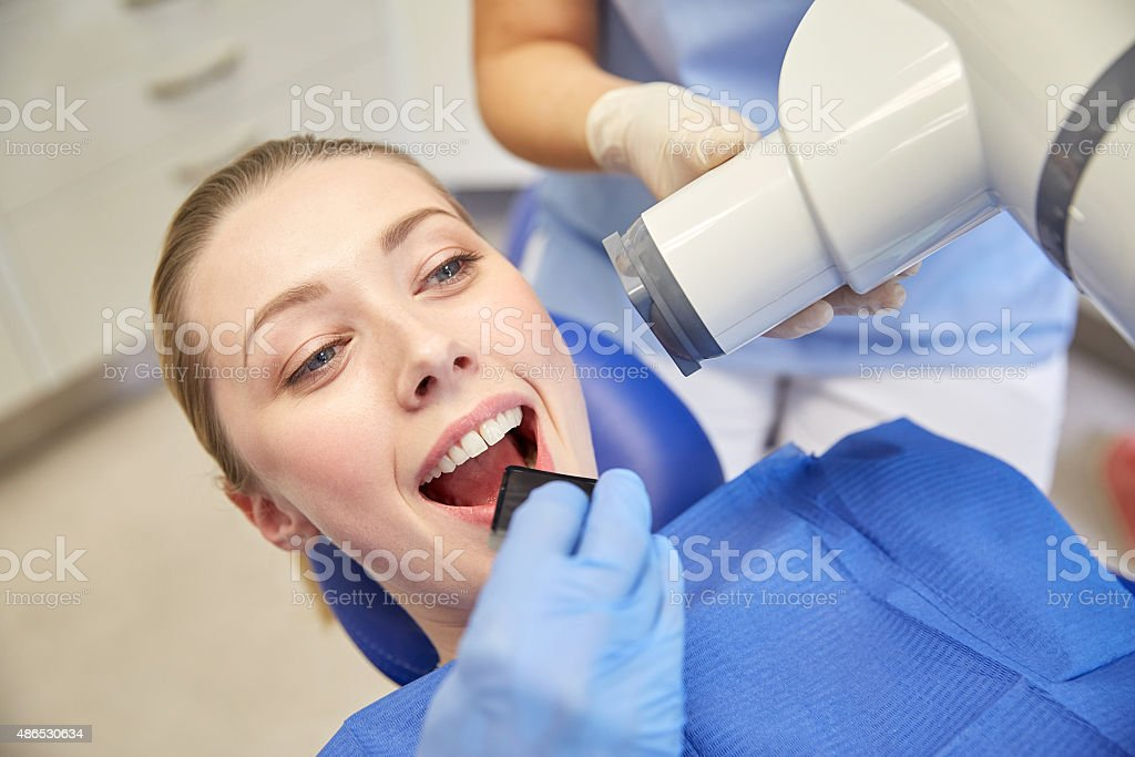 female patient face with x-ray machine and shield stock photo