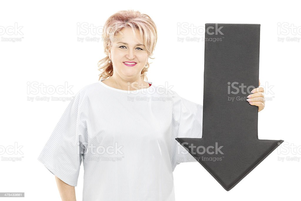 Female patient in hospital gown holding big black arrow stock photo